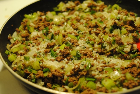 Cooking beef, vegetables, rice, and dill together for stuffed cabbage rolls (photo)